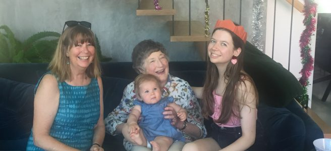 Baby girl, young woman, older woman and elderly woman sitting on a couch smiling