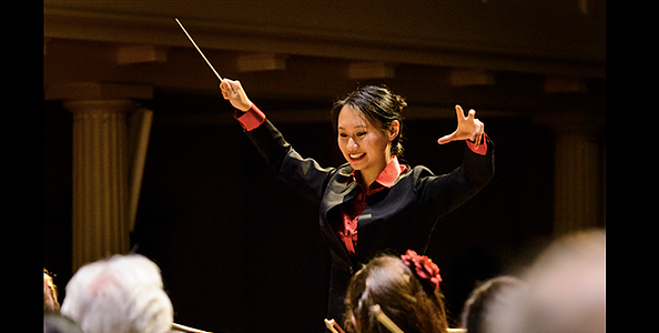 Young woman conducting an orchestra and smiling