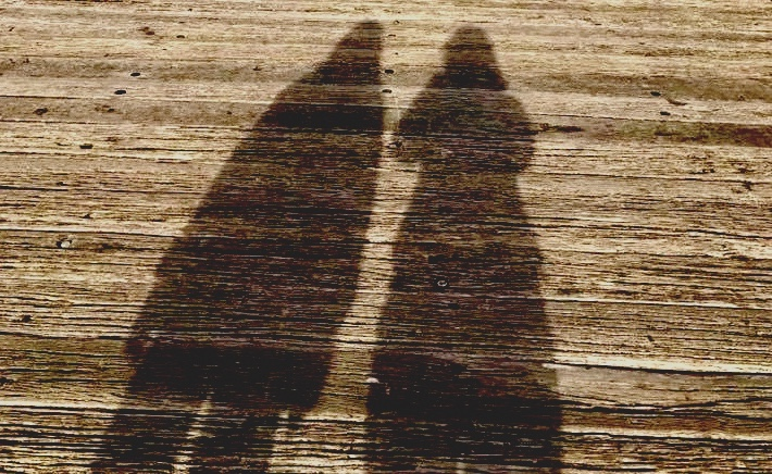 The shadows of two women on timber decking