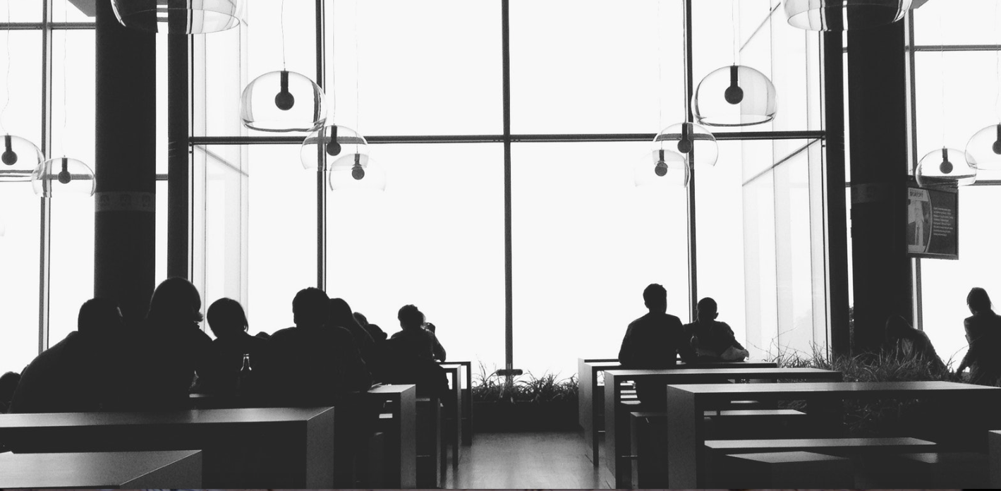 Black and white photo of a cafeteria with long tables and people sitting at them