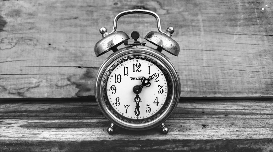 Black and white  photo of an alarm clock on a timber shelf