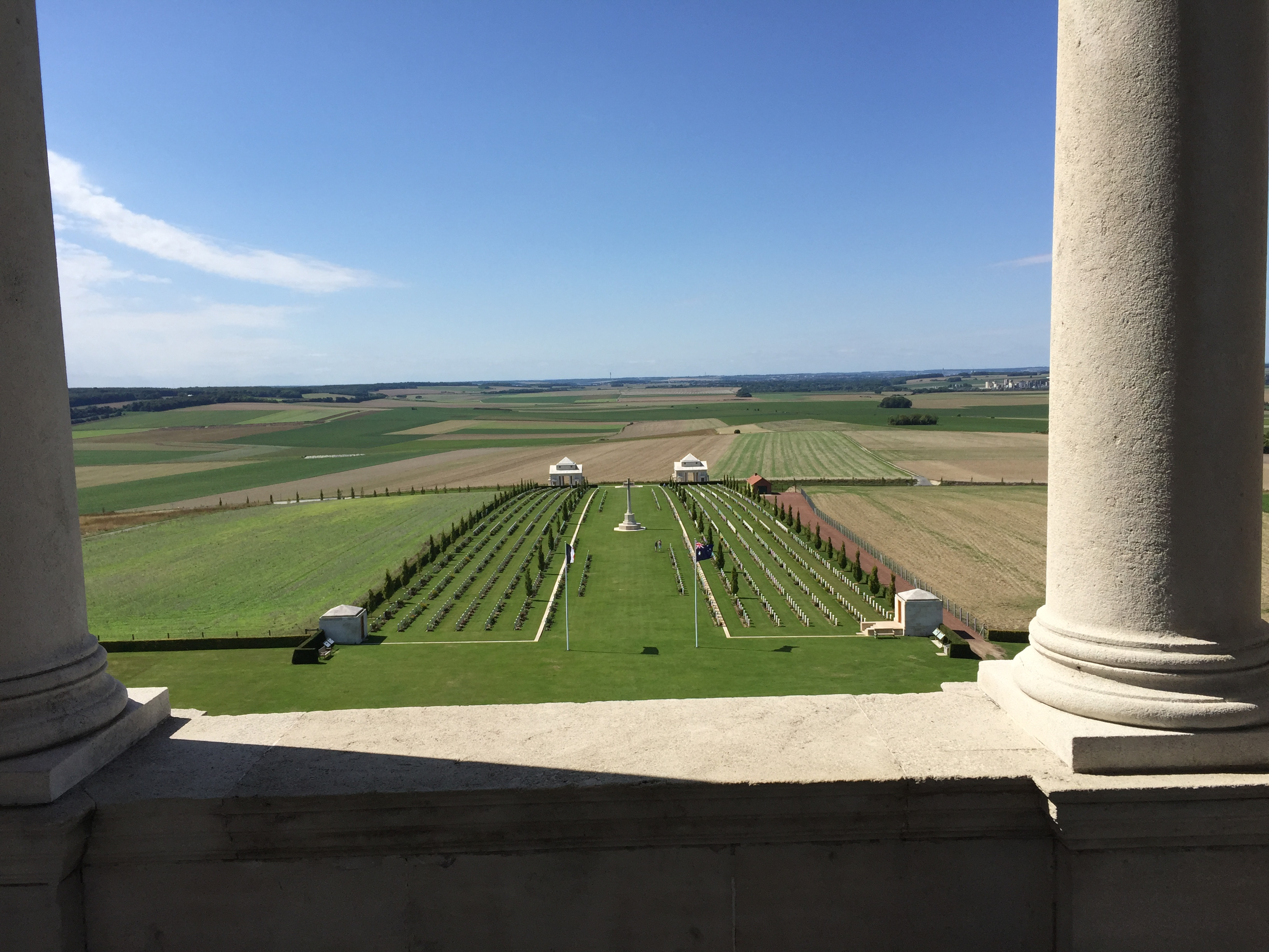 The view looking out on a sunny day with blue skies over rolling hills. In the foreground are rows of headstones on a lawn.