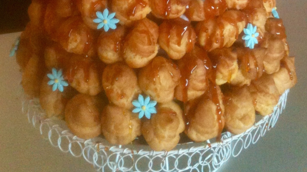 The lower half of a croquembouche showing profiteroles, toffee and blue sugar flowers.