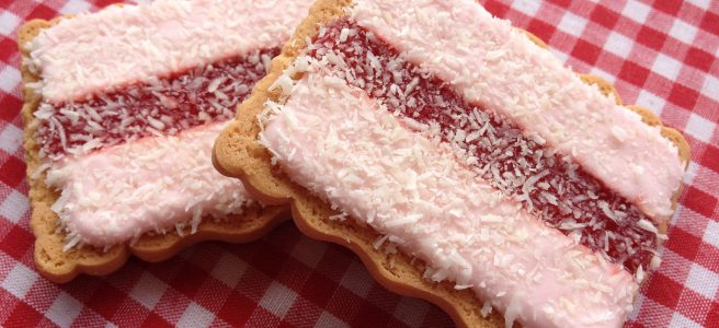 Old-fashioned iced vovos - a rectangular biscuit base topped with a red stripe of jam flanked by pink icing and sprinkled with shredded coconut