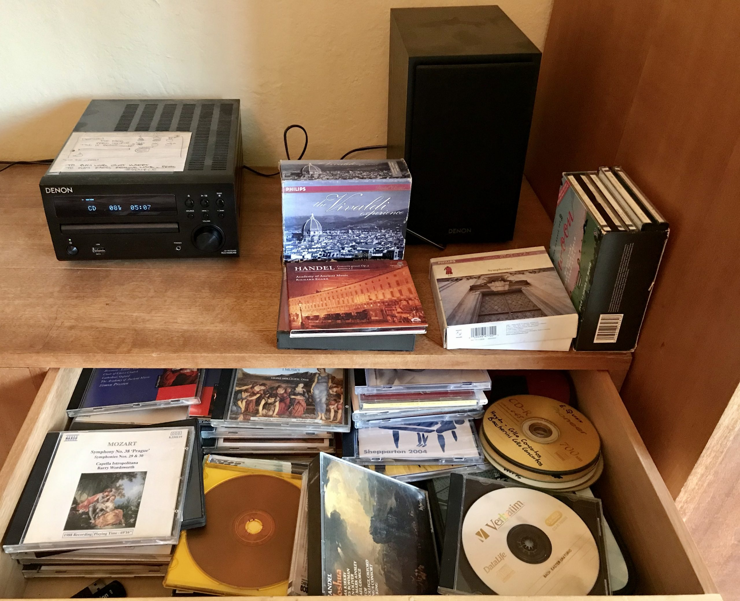 A drawer full of Cds, a CD player and speaker on the bench above it.