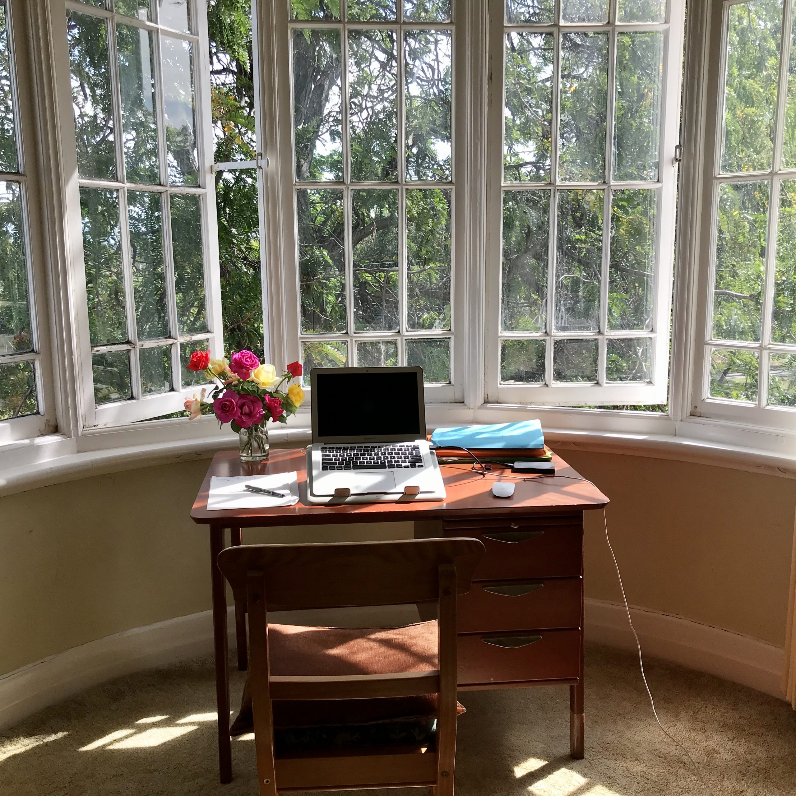 A desk in front of open casement windows with a laptop and a vase of roses