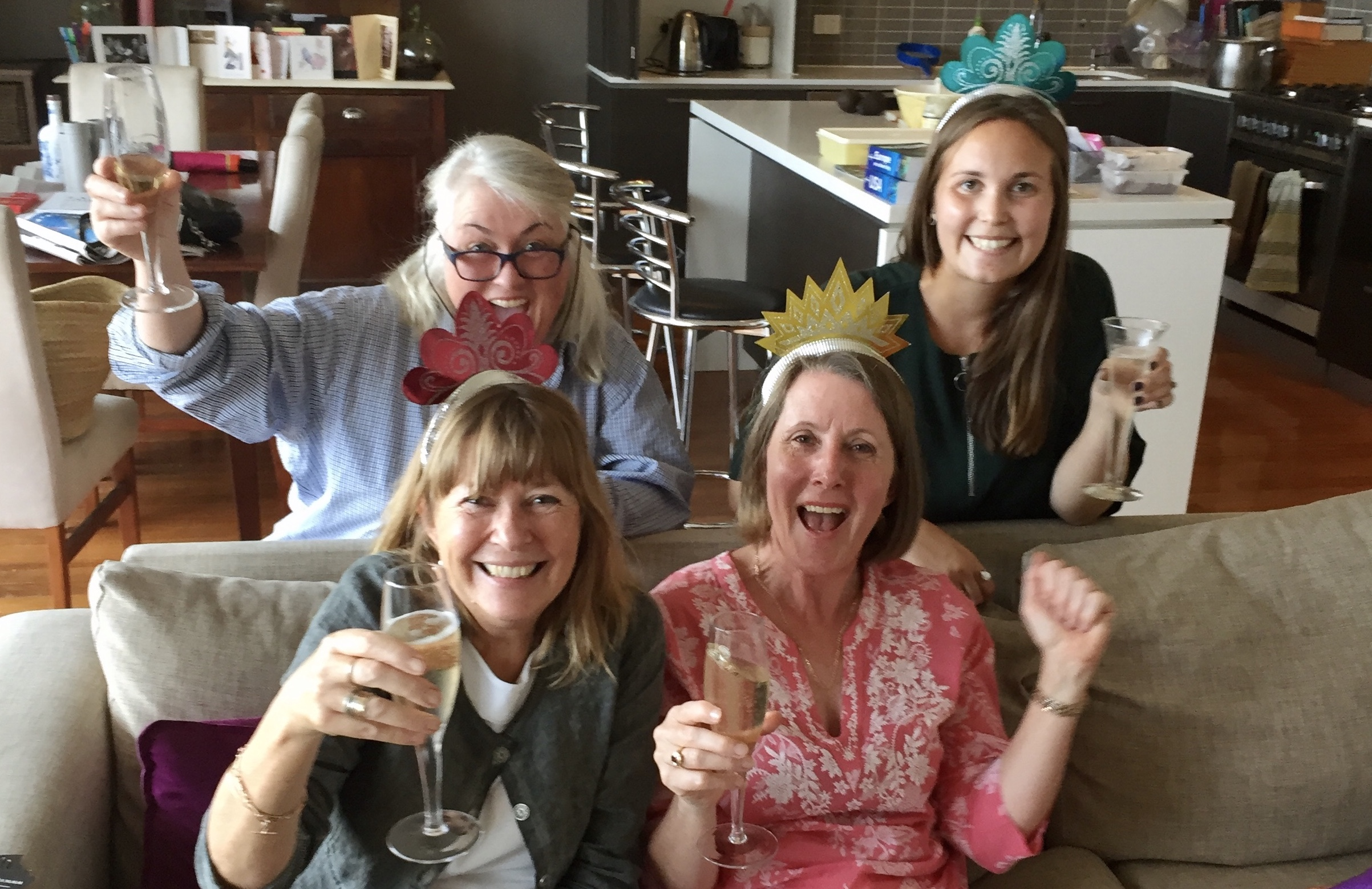 Four women in tiaras on a couch holding glasses of champagne