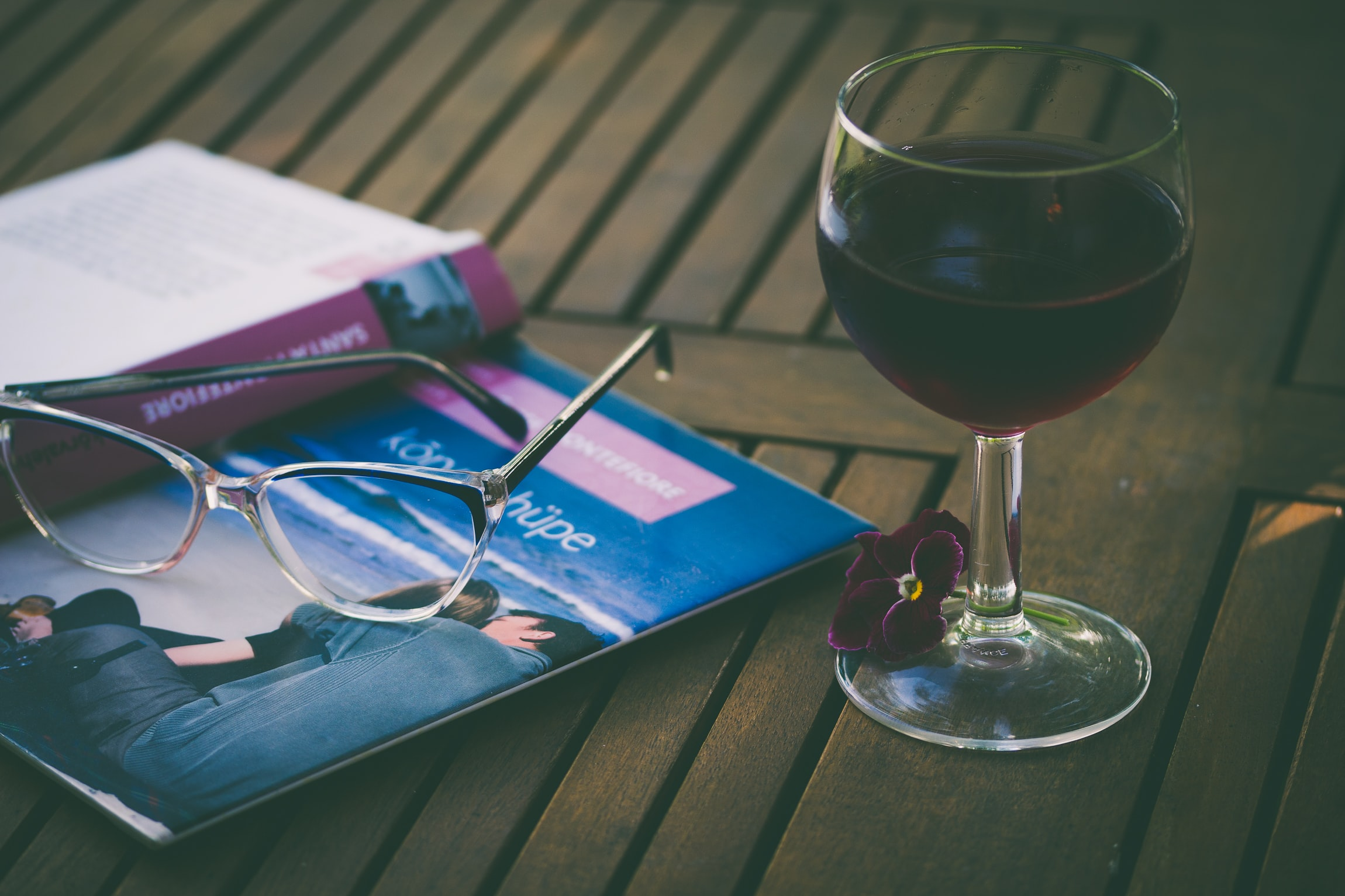 A pair of glasses atop an open book next to a glass of red wine