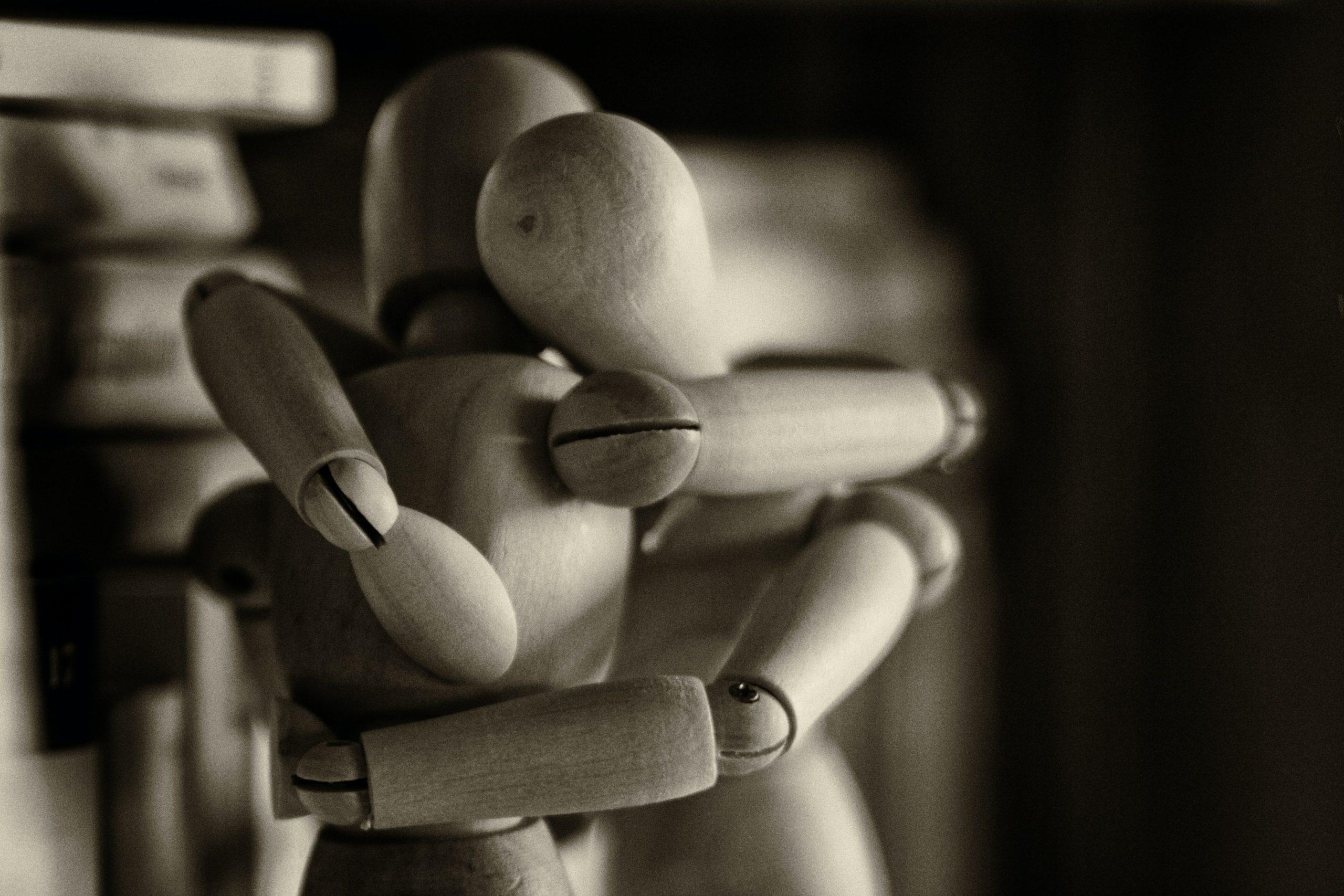 Two wooden dummy figures hugging