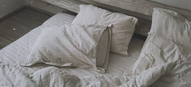 An unmade bed  that looks as though someone has just leaped out of it.