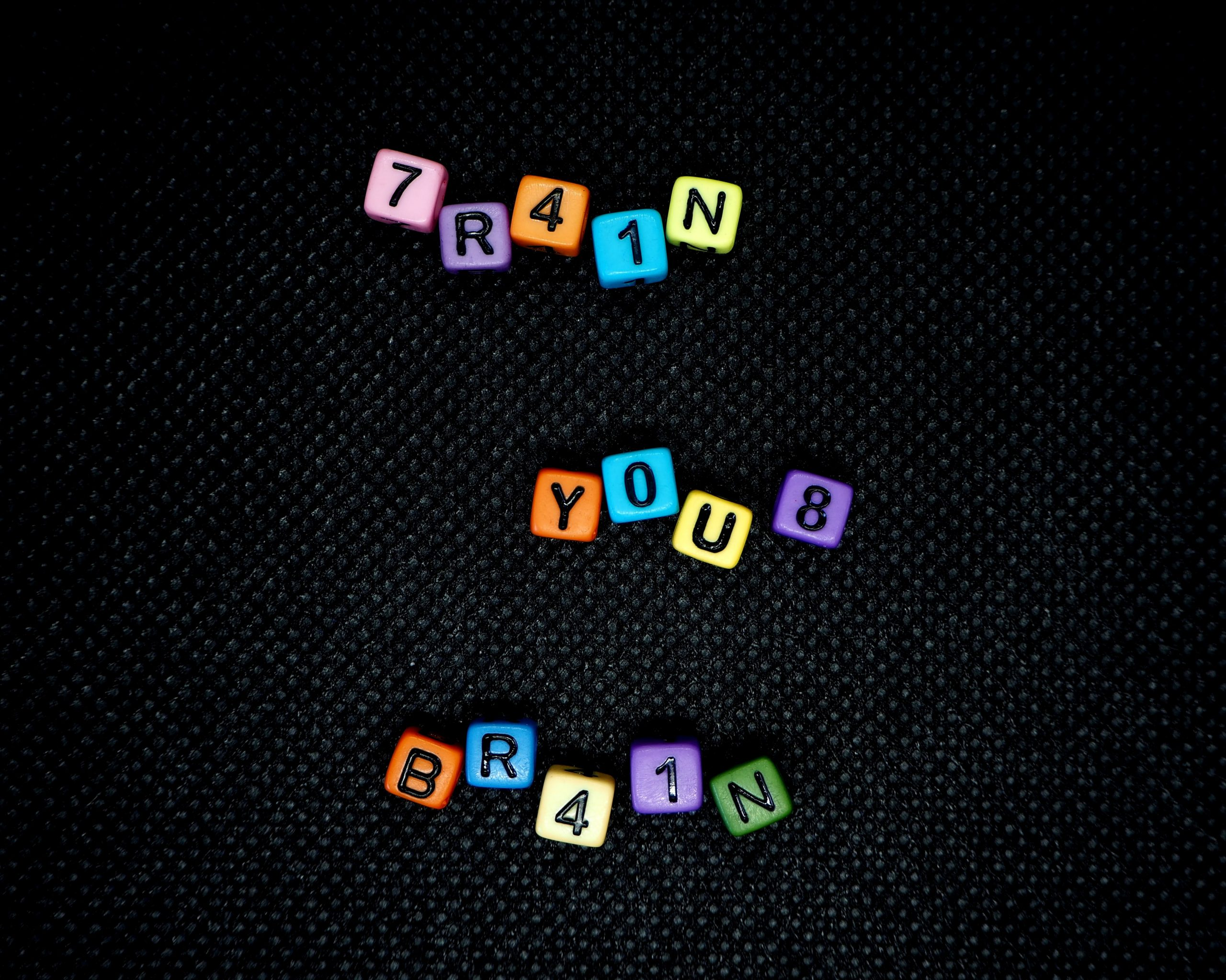 A black board with coloured blocks spelling out Train Your Brain