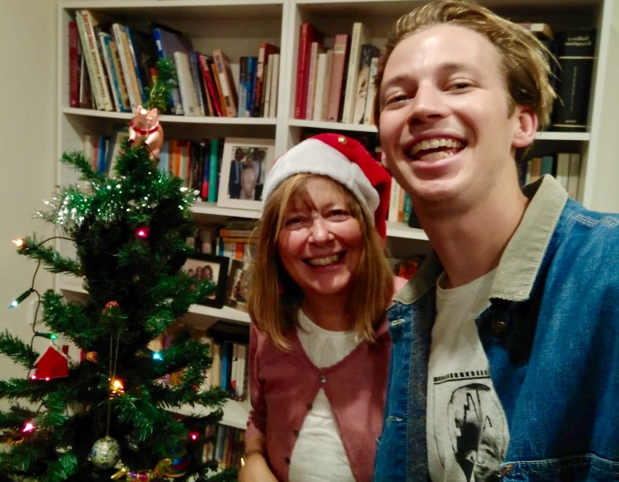 A mother and son smiling in front of a Christmas tree